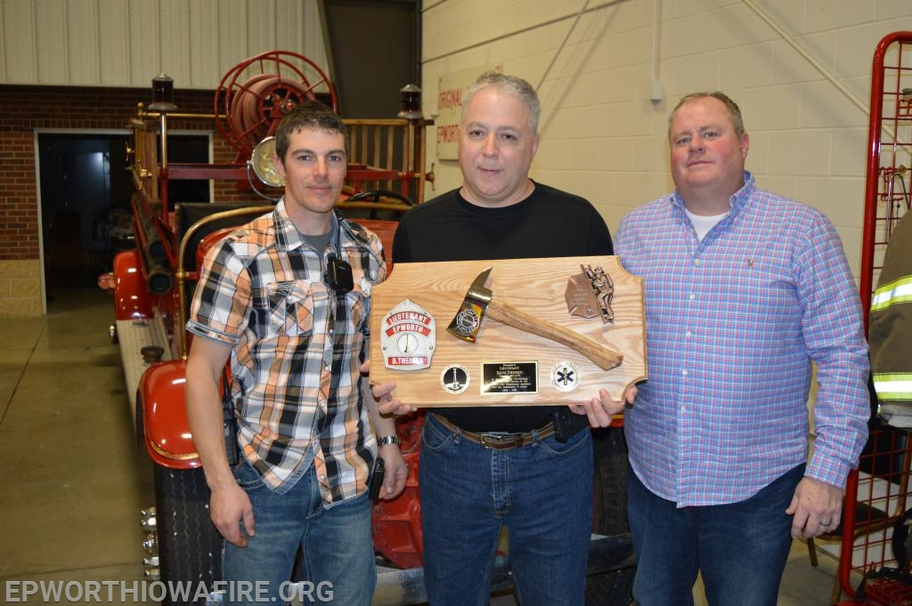 Lt. Dave Theisen retired in 2018 after 30 years of service and was given a retirement axe.  Pictured are President Kyle Mueller, Dave Theisen and Fire Chief Tom Berger.